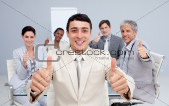 Attractive businessman and his team with thumbs up