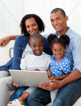Smiling Afro-american family using a laptop