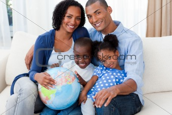 Afro-american family holding a terrestrial globe
