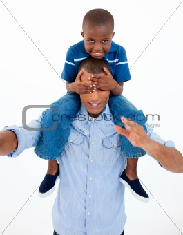 Dad giving son piggyback ride with closed eyes