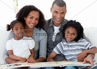 Portrait of an Afro-American family reading a book in the living