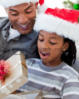 Portrait of an Afro-American father and son opening a Christmas