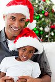 Afro-American dad and daughter wearing a Christmas hat