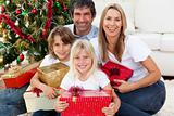 Smiling family holding Christmas presents