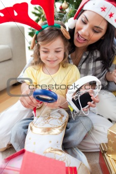 Mother and daughter playing with Christmas presents