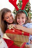 Smiling mother and her daughter holding Christmas gifts