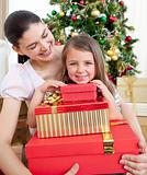 Mother and daughter at home holding a Christmas gift