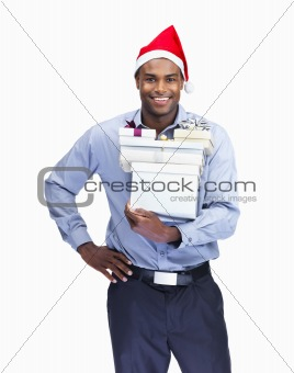 A smiling business man with Christmas gifts on white
