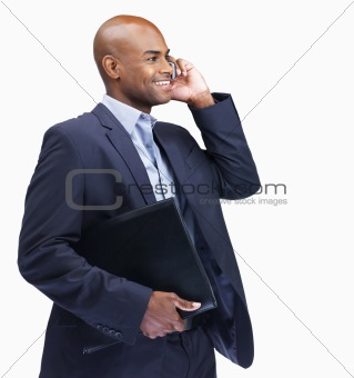 Business man with folder while talking on cellphone