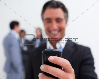 Smiling businessman sending a text with a mobile phone