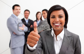 Attractive female executive smiling at the camera with thumb up
