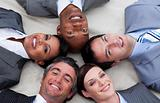 Multi-ethnic business team lying on the floor with heads togethe