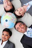 Multi-ethnic business team lying on the floor around a terrestri