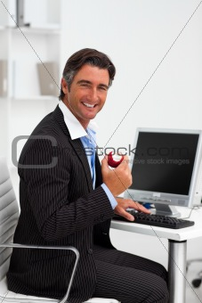 Smiling businessman holding a red apple