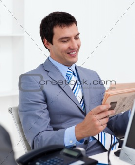 Attractive young businessman reading a newspaper