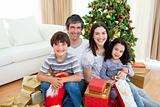Young business people workin  Young family having fun with Christmas presents at homeg together in office