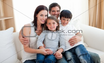 Portrait of a smiling family sitting on the sofa