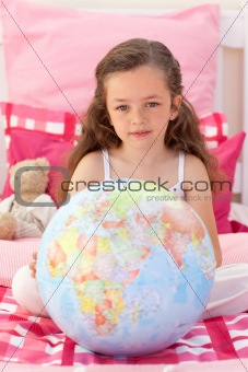 Little girl holding a terrestrial globe