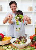 Happy father and his son preparing a salad
