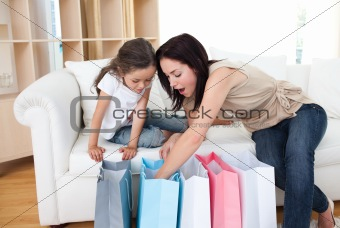 Mother and daughter unpacking shopping bags