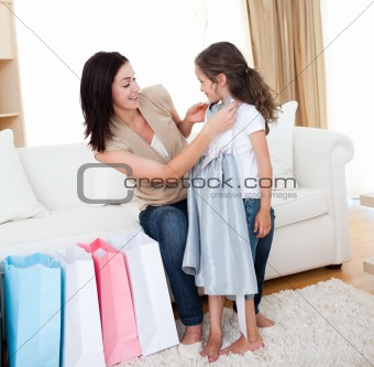Happy Mother and daughter unpacking shopping bags in the living-room