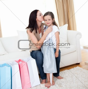 Mother kissing her little girl after shoppi