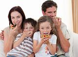 Happy family eating pizza in living-room all together