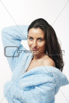 attractive brunette in blue bathrobe with hood isolated on white