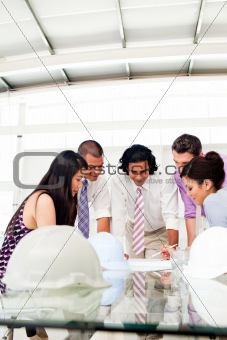 International engineers and their manager discussing blueprints