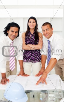 Portrait of architects studying plans in a meeting