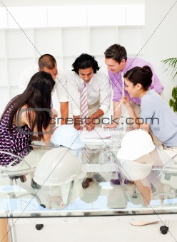 A team of architects at the meeting looking at blueprints
