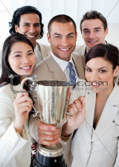 A successful business team holding a trophy