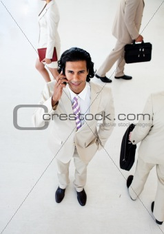 Attractive businessman on phone smiling at the camera