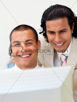 Smiling businessman helping his colleague at a computer