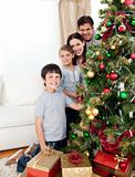 Happy family decorating a Christmas tree with boubles and presen