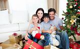 Young family having fun with Christmas presents at home