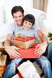 Happy father and son holding Christmas gifts