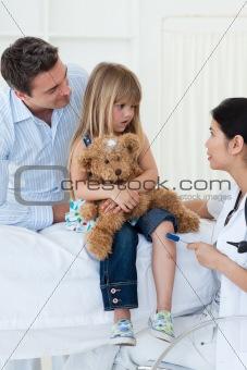 Confident female doctor checking little girl's reflex