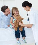 A doctor examining smiling child and playing with a teddy bear