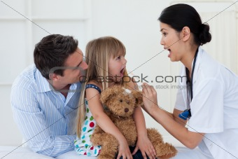 Little girl opening her mouth and the doctor checking her throat