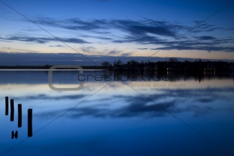 Calm sunrise over a lake with clouds reflection in the water