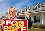 Beautiful Female Holding Keys to a New House &amp; Sold Real Estate Sign.