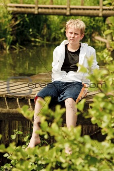 Portrait of young boy sitting on a bridge
