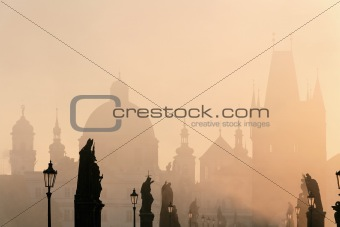 prague - charles bridge and towers of the old town on foggy morning