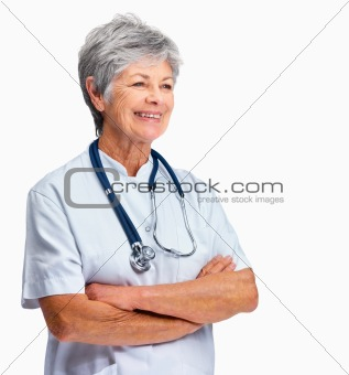 Happy senior nurse with hands folded and looking at copyspace