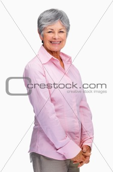 Lovely old woman standing isolated over white background