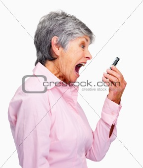 Side view of a angry senior woman screaming in her cellphone