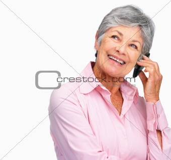 Happy senior woman using a cellphone by copy space
