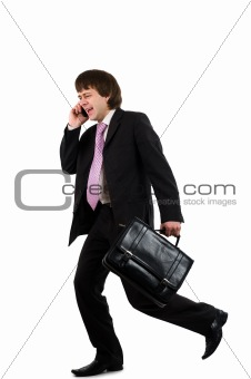Business man running with a briefcase and speaking by phone