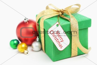 Green Christmas gift with ornament and tag